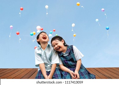 Funny Asian little kids brother and sister sitting on the wooden terrace with colourful balloons background.laughing and Happiness of cute kid in uniform school,Education,Family,Children Concept.