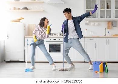 Funny asian loving couple singing songs while cleaning kitchen, using broom and mop as microphones, cheerful beautiful young man and woman imitating rock stars while house-keeping, copy space