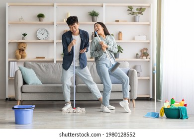 Funny asian loving couple singing songs while cleaning apartment, using broom and mop as microphones, cheerful beautiful young man and woman imitating rock stars while house-keeping, copy space