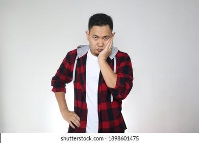 Funny asiatischer Mann mit verärgertem, verärgertem Ausdruck, der die Kamera auf grauem Hintergrund betrachtet