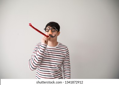 Funny Asian man with party whistle for April Fools' Day prank on light background