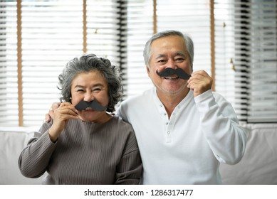 Funny Asian Senior Couple are holding paper mustache and pretending of men. Family holiday and togetherness.