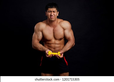 Funny Asian tensed man with closed eyes tries to lift a dumbbell. crazy bodybuilder pretending that holding heavy dumbbell. entertainment, joke concept. isolated black background.