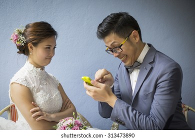 Funny Asian wedding photo shooting with groom playing smartphone while bride looking angrily