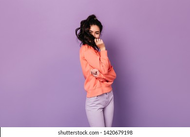 Funny asian woman in casual attire playing with hair. Studio shot of wonderful korean girl isolated on purple background.