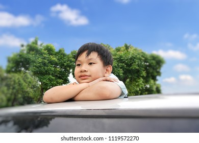 Funny Asian young boy standing on the sunroof of the car with cloud,tree and blue sky background.Smiling and Happiness of cute kid in the summer.Holiday,Vacation,Family,Travel Concept.