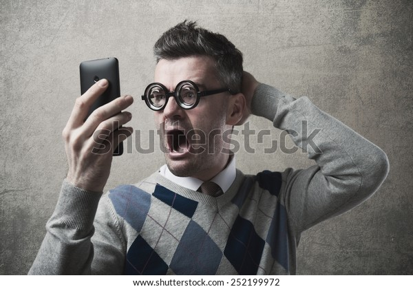 Funny astonished angry guy having troubles with his smartphone