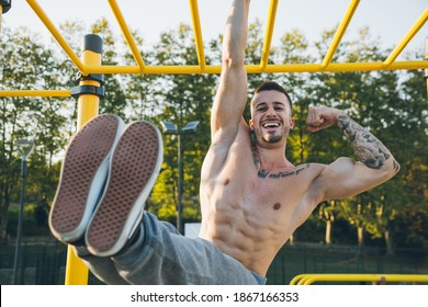 Funny athletic young man hanging from the bars showing his muscles and strength at the calisthenics gym outdoors smiling