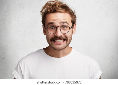 Funny attractive bearded young male with comic smile, has awkward look, pretends to be happy, looks gladfully through round spectacles, laughs at joke, isolated over white concrete background.