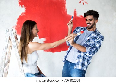 Funny attractive couple playing with color brushes while painting home