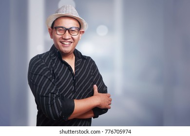 Funny attractive cute Asian man wearing eyeglasses and panama hat smiling with arms crossed