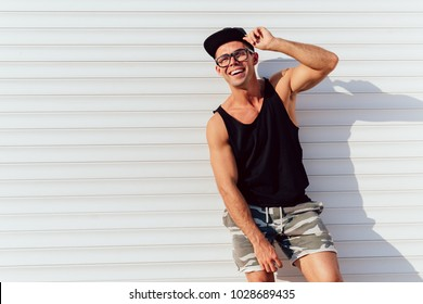 Funny attractive man in eyeglasses posing near the urban wall, wearing black singlet, shorts and cap. Outdoors.