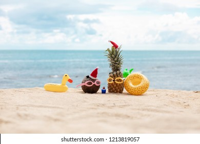 funny attractive pineapple and coconut in stylish sunglasses on the sand against turquoise sea. Wearing christmas hats. Christmas and new year vacation concept on tropical beach. Family holiday.