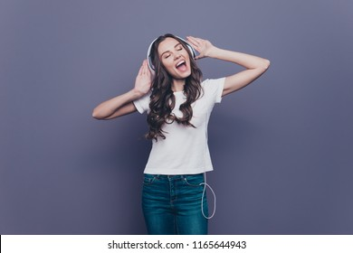 Funny attractive pretty lovely stylish nice cheerful curly-haired brunette girl in casual white t-shirt and jeans, listening to music, dancing, isolated on grey background