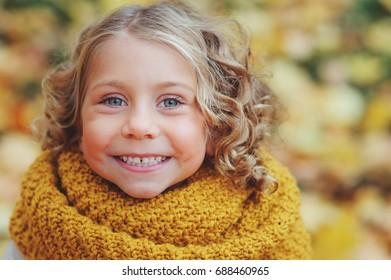 funny autumn portrait of happy toddler girl walking outdoor in stylish orange snood