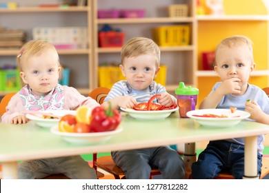 funny babies group eating vegetables in kindergarten dinning room