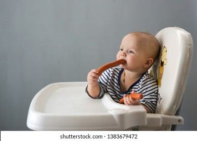 Funny baby 10 months eating sausages in the highchair, unhealthy food. The child eats sausages
