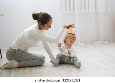 Funny baby 10 months with his mother playing with a pot in the kitchen, lifestyle in the real interior in the Scandinavian style, day light