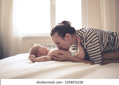 funny baby 6 months old with mom on a bed in a real room. Mom tickles and gently kisses the baby. Concept maternal love and motherhood, soft focus, toning and lifestyle