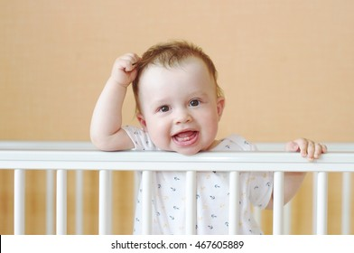 funny baby age of 9 months in white bed
