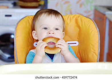 funny baby boy age of 1 year eating round cracknel on kitchen