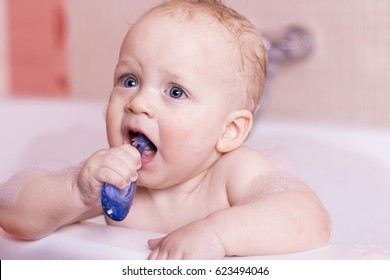 Funny baby boy brushes his teeth. Blue-eyed awesome inafnt kid brushing teeth first time.