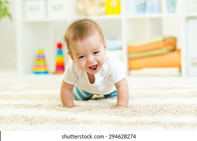 funny baby boy crawling on carpet at home