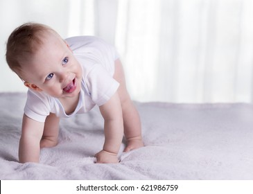 Funny baby boy on knees trying to walk. Awesome infant kid on all fours. Smiling toddler and his first steps