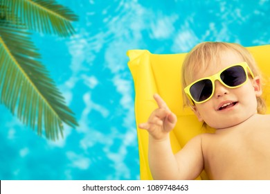 Funny baby boy on summer vacation. Child having fun in swimming pool