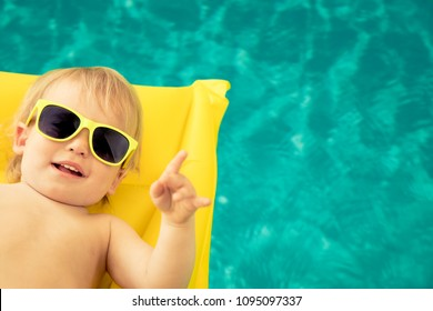 Funny baby boy on summer vacation. Kid having fun in swimming pool