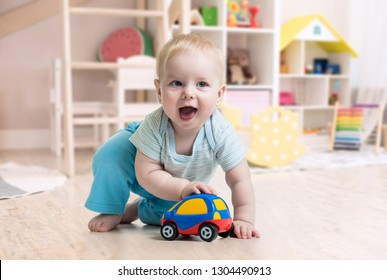 funny baby boy playing toy in nursery or kindergarten