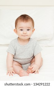 Funny baby boy sitting on the bed