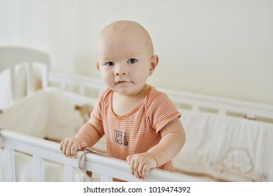 funny baby boy standing in the bed