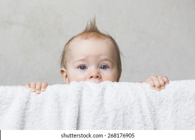 Funny baby boy toddler peeking out of the crib. Hairstyle hair stick
