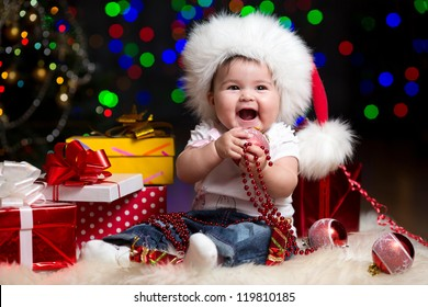 funny baby dressed in Santa Claus hat on bright festive background