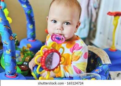 funny baby with dummy in baby jumper