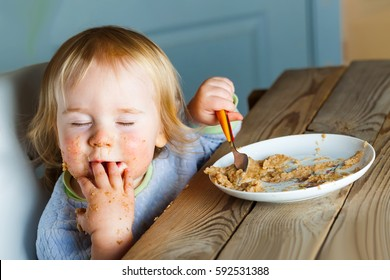 Funny Baby eats porridge spoon mashed