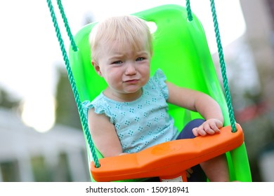 Funny baby girl with emotional face playing outdoors sitting on a swing at playground in the city park