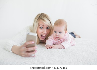 Funny baby girl make selfie on mobile phone and lying near her mother. Newborn looking at the camera and smiling.