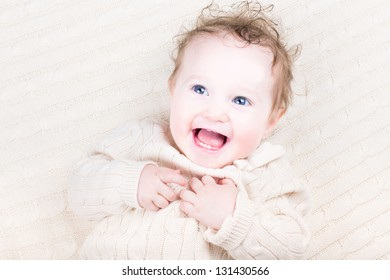 Funny baby girl on a cable knit blanket