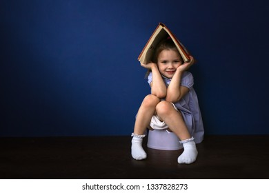 Funny baby girl playing in a house with a book, concept of cognitive activity and safety