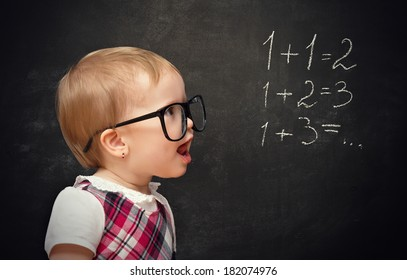 Funny baby girl pupil solves arithmetic examples on blackboard