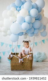 funny baby girl sitting in a wicker basket with balloons on a white background