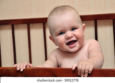 funny baby holding bed grating and smiling