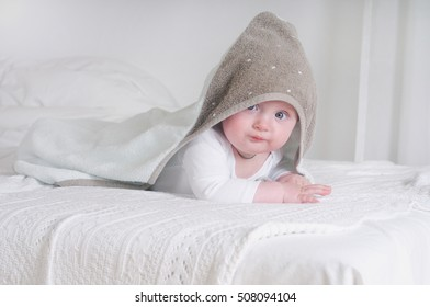 Funny baby kid under a hooded towel. Happy family concept