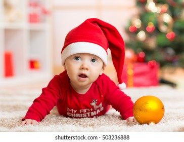 funny baby lying on tummy wearing santa hat and suit on floor in front of christmas