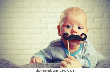 funny baby with a mustache on the brick wall background