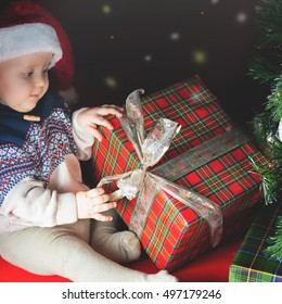 Funny baby opening a gift box at Cristmas. Dressed at Santa hat. Christmas family celebration