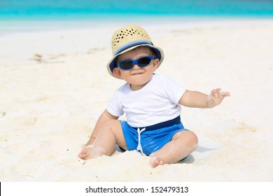Funny baby with panama hat and sunglasses having tropical vacation