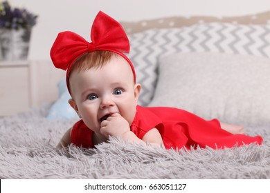 Funny baby in red dress and bow with hand in mouth is on bed with pillows in bedroom